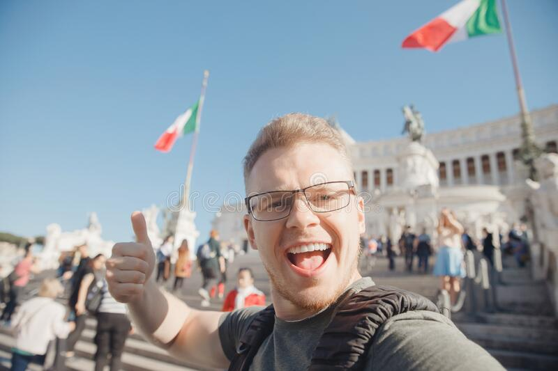 Happy male tourist taking selfie photo on background Venice Square in Rome Italy, blue sky. Travel concept stock image
