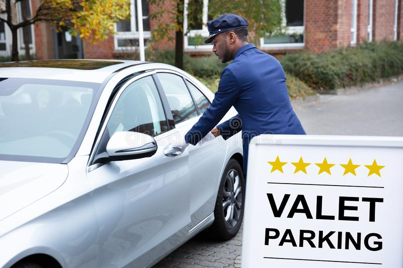 Happy Male Valet Opening Car Door royalty free stock image