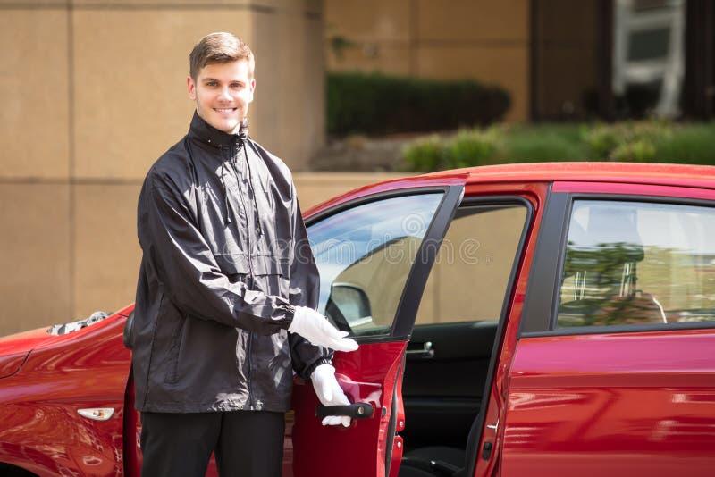 Happy Male Valet Opening Car Door royalty free stock photo