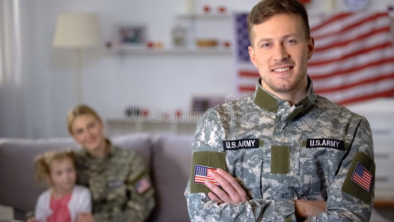 Happy male veteran of US army smiling at camera, wife and daughter on background. Stock photo stock photos