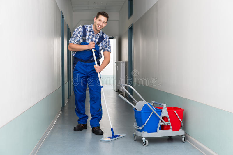 Happy male worker with broom cleaning office corridor. Full length portrait of happy male worker with broom cleaning office corridor stock photography