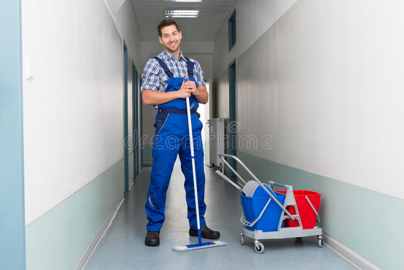 Happy male worker with broom cleaning office corridor. Full length portrait of happy male worker with broom cleaning office corridor royalty free stock photography