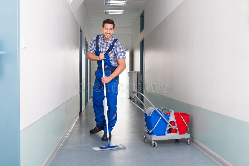 Happy male worker with broom cleaning office corridor. Full length portrait of happy male worker with broom cleaning office corridor stock image