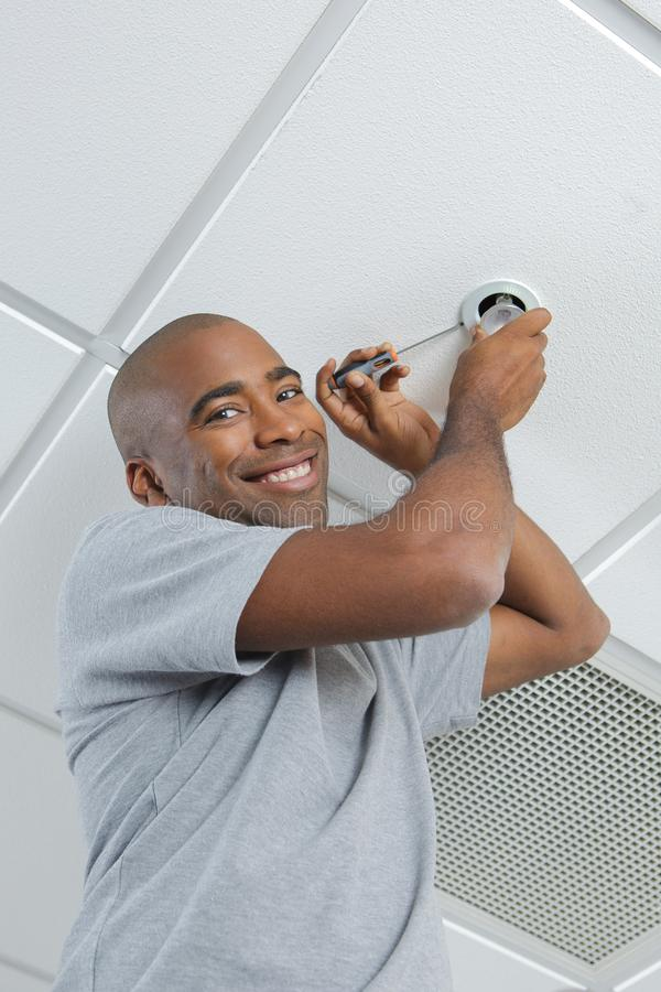 Happy male worker fixing sprinkler stock images