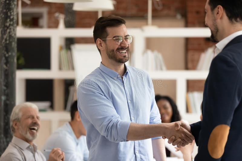 Happy male worker get promoted rewarded handshake manager in office. Happy male worker feel excited get promoted rewarded being best employee handshake manager stock photography