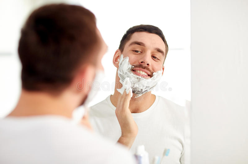 Happy man applying shaving foam at bathroom mirror stock photo