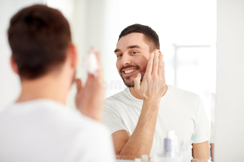 Happy man applying shaving foam at bathroom mirror. Beauty, hygiene, shaving, grooming and people concept - smiling young man looking to mirror and applying stock photography