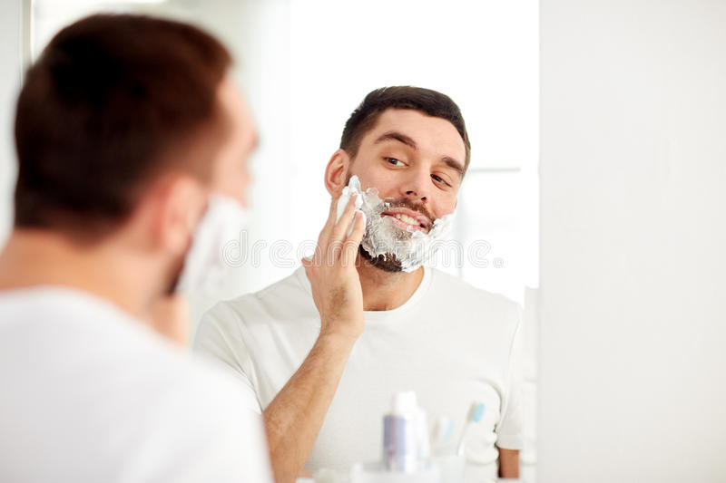Happy man applying shaving foam at bathroom mirror. Beauty, hygiene, shaving, grooming and people concept - smiling young man looking to mirror and applying royalty free stock image