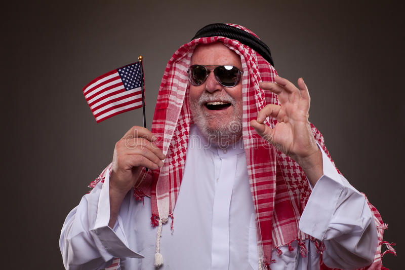 Happy man in Arabic clothing with American flag stock photo