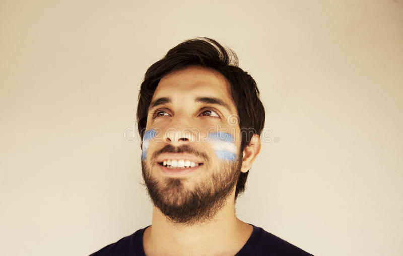 Happy man with Argentinian flag. Painted on face stock photography