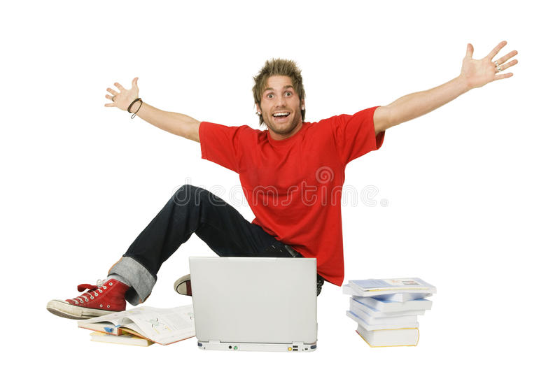 Happy man with arms raised. Excited young man with arms raised sitting in front of laptop and stack of books stock photography