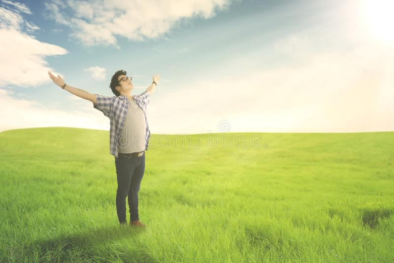Happy man with arms wide open enjoying spring on green meadow. Summer or Spring concept royalty free stock photos