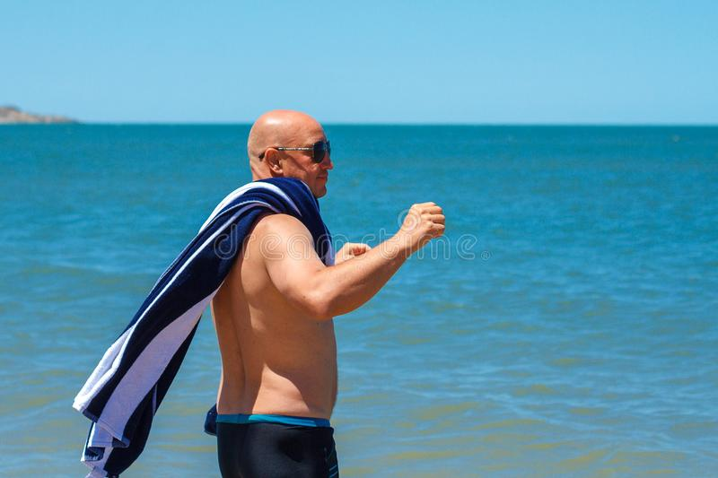 Happy man on the beach enjoys the freedom of the concept of rest and vacation stock photo
