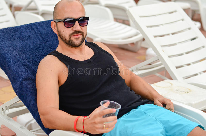 Happy man. Beautiful smiling tanned bearded muscular man relaxing on the pool and drinking beer stock photography