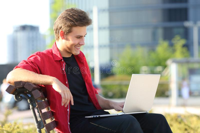 Happy man on a bench using a laptop in a park stock images