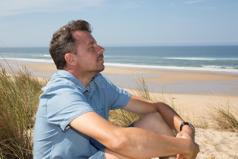 Happy man breathing deep on the beach in vacation stock image