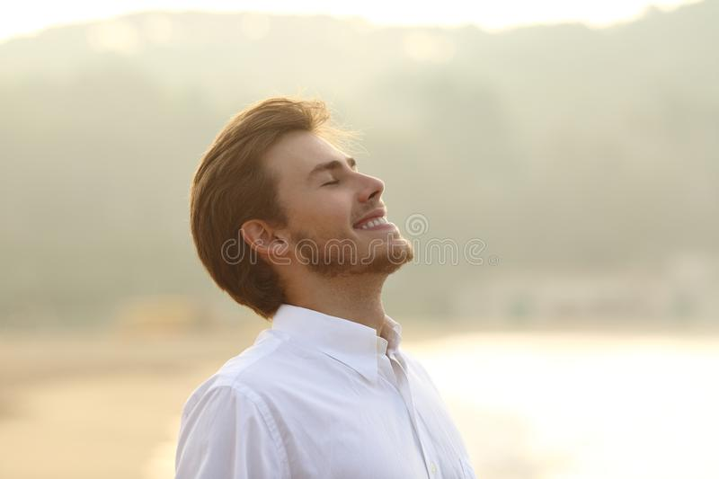 Happy man breathing deep on the beach in vacation. With a yellow background isolated on white above stock photo