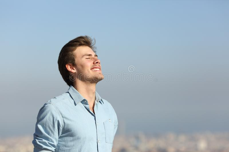 Happy man breathing deeply fresh air outskirts. Happy man breathing deeply fresh air in the city outskirts royalty free stock images