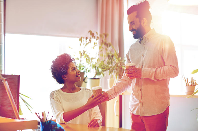 Happy man bringing coffee to woman in office royalty free stock photo