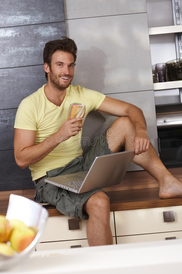 Download Happy Man Browsing Internet In Kitchen Stock Image - Image: 29137007