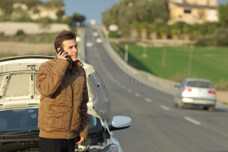 Happy man calling roadside assistance for his breakdown car. In a country road royalty free stock image