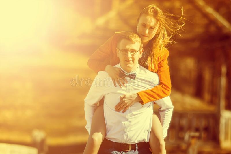Happy man carrying his girlfriend on the back on on the bridge o stock photography