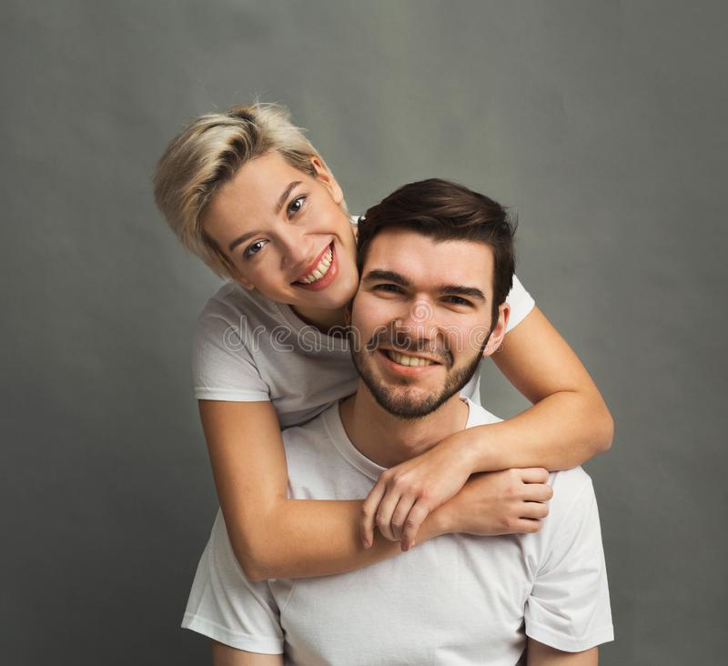 Happy man carrying his girlfriend on back royalty free stock image