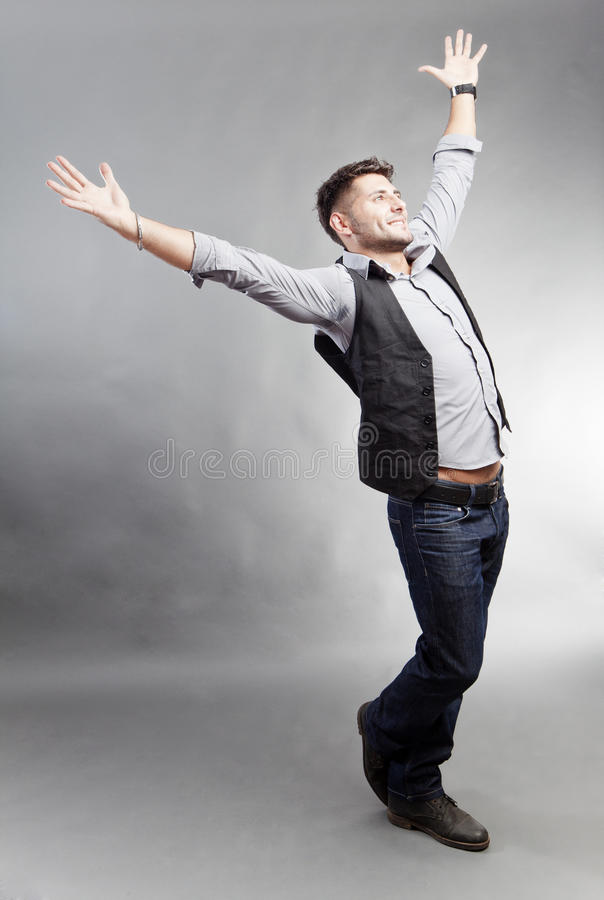 Happy man in casual clothes. With outstretched arms, studio background royalty free stock photos