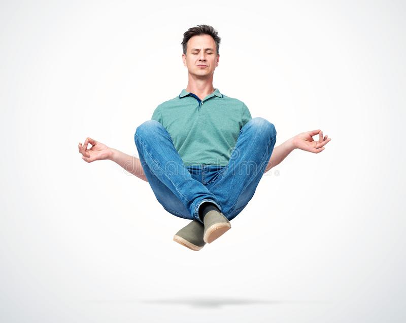 Happy man in casual clothes closing his eyes meditating levitating in the air. Comprehended relaxation royalty free stock image