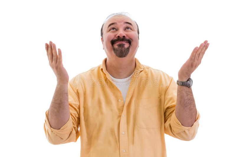 Happy man celebrating a success or solution. Happy middle-aged man standing celebrating a success or solution raising his hands to heaven in thanks and praise royalty free stock photography