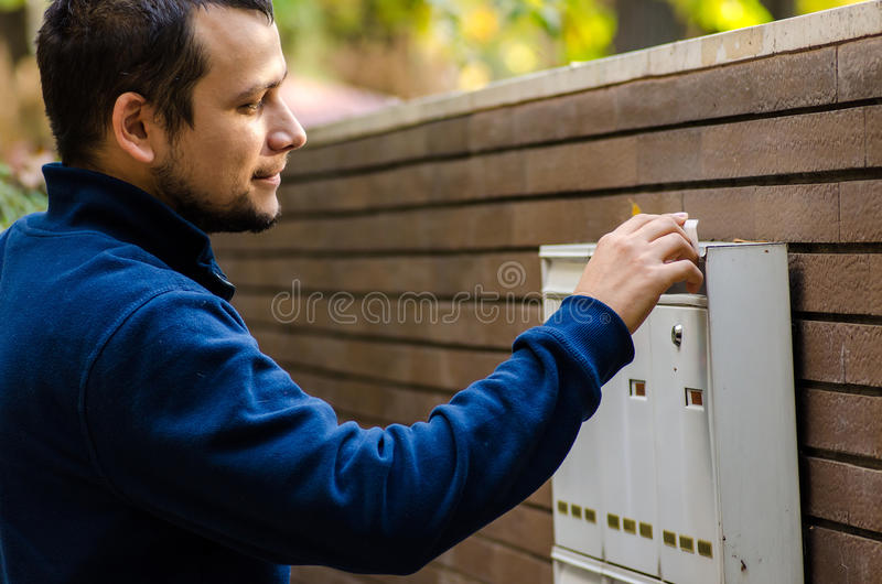Happy man checking mail box. Optimistic young man checking mail box royalty free stock photography