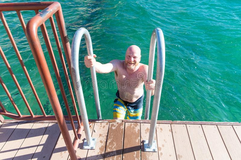 Shirtless, bald man climbing out of lake on a ladder. Happy man climbing a ladder to get out of water royalty free stock images