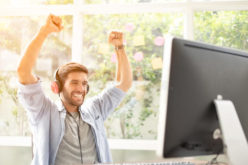 Happy man completed task and triumphing with raised hands and screaming royalty free stock photo