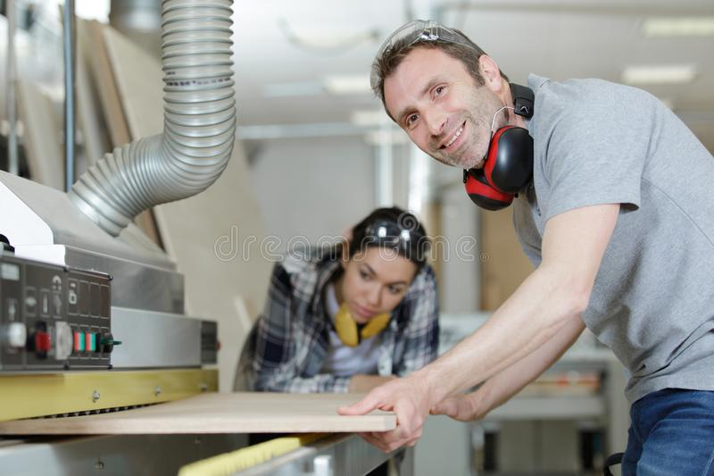 Happy man cutting wood indoors royalty free stock photo