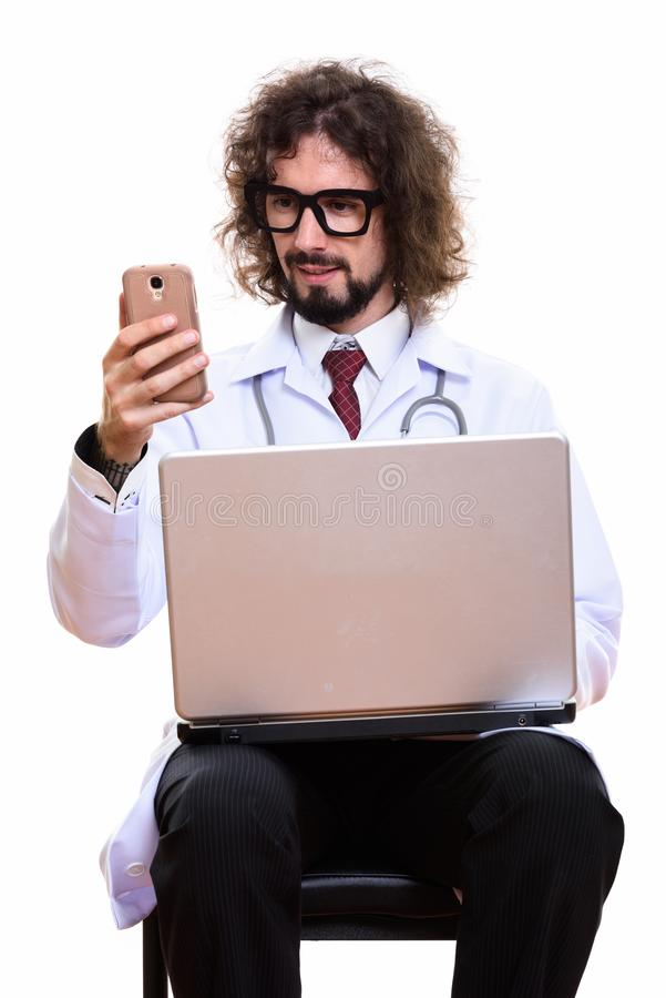 Happy man doctor smiling while using mobile phone with laptop. Isolated against white background royalty free stock image