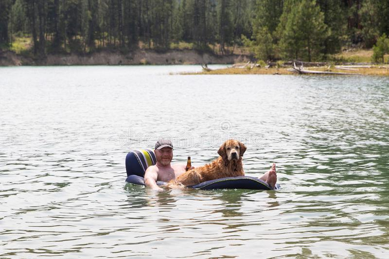 Happy man drinking a beer and floating on a lake with his golden retriever dog stock photos