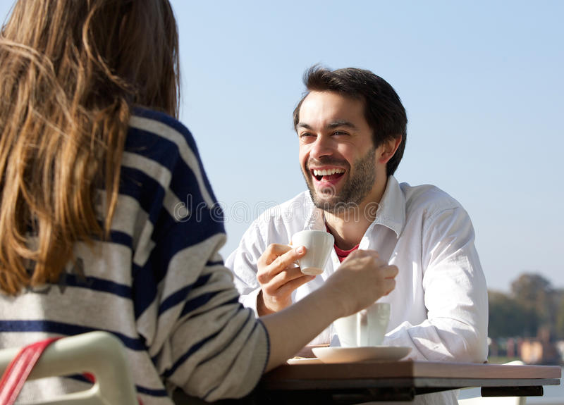 Happy man drinking coffee with woman at outdoor cafe stock photo