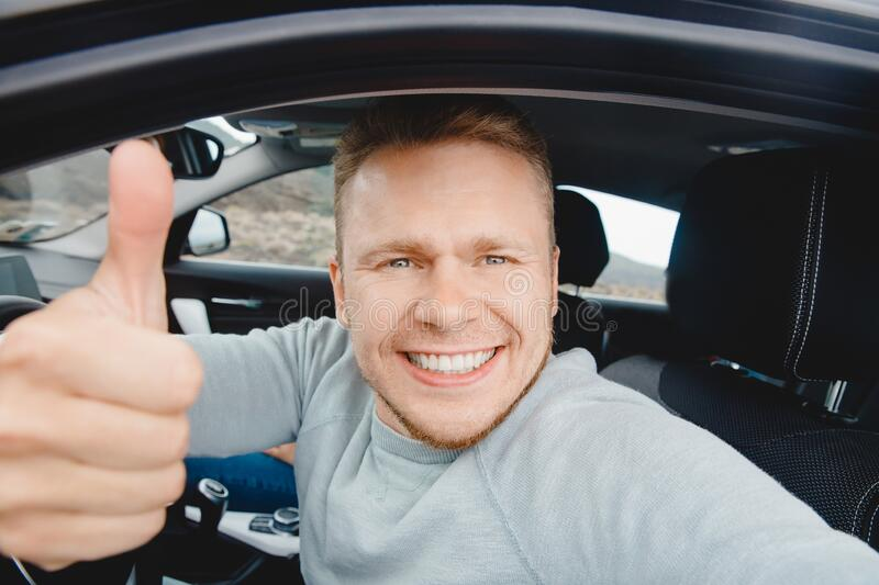 Happy man driver buyer car looking camera and taking selfie photo, beautiful smile. Concept preparing for road trip royalty free stock photography