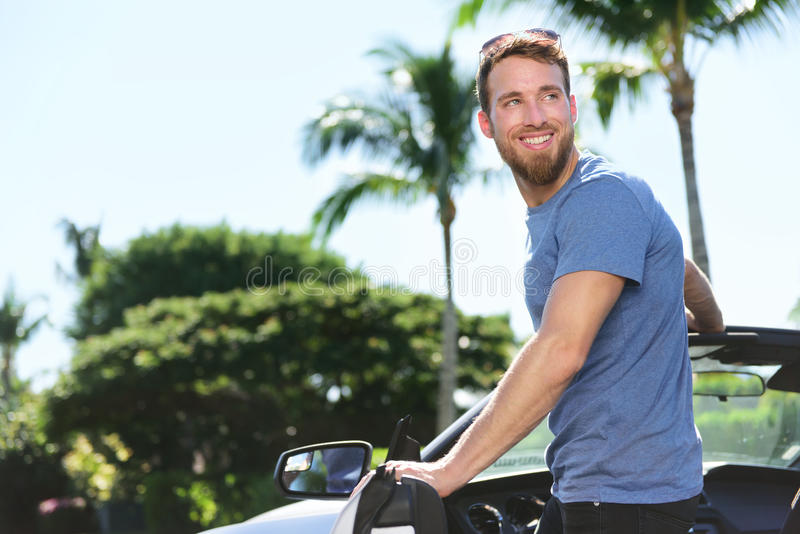 Happy man driver driving his new convertible car. Young male adult new owner going in his luxury car for a ride or road trip during a summer day stock image