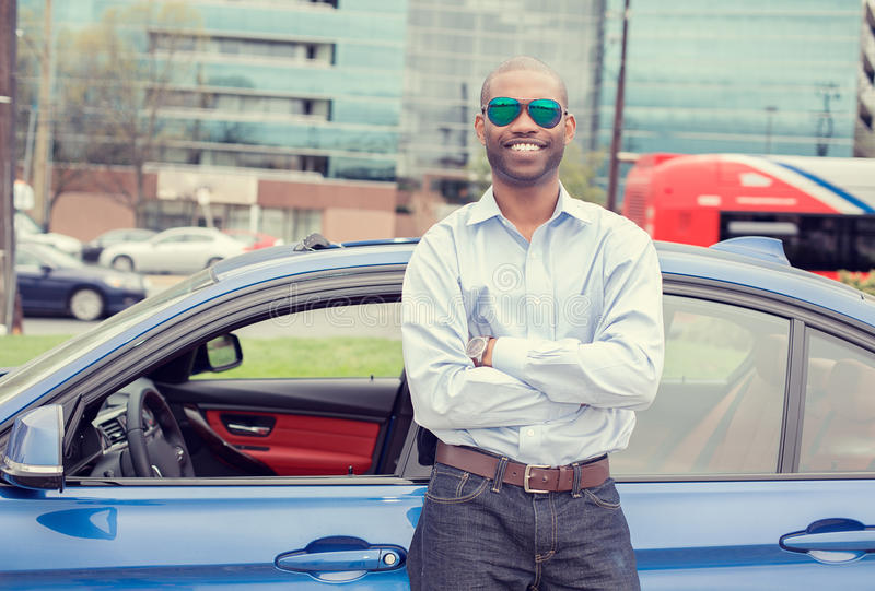 Happy man driver smiling standing by his new sport blue car. Outside parking lot background. Handsome young man excited about his new vehicle. Positive face stock photos