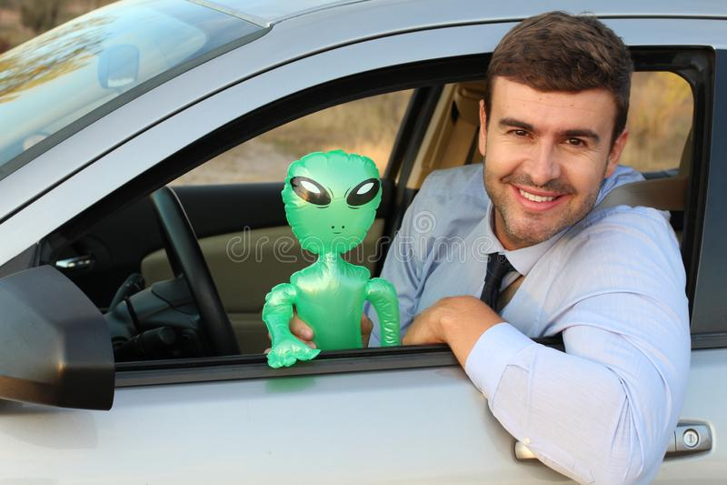 Happy man driving with an alien royalty free stock photo
