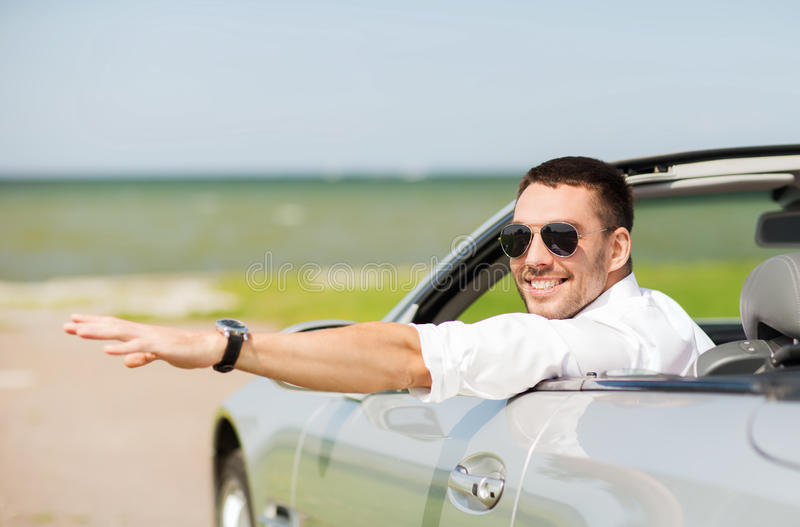Happy man driving cabriolet car and waving hand royalty free stock image