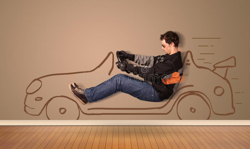 Happy man driving an hand drawn car on the wall stock photography