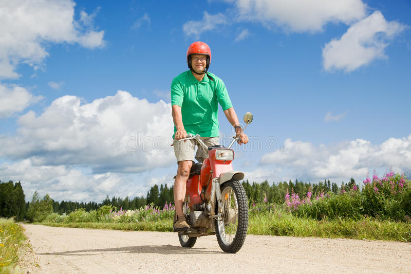 Happy man driving a moped royalty free stock photos