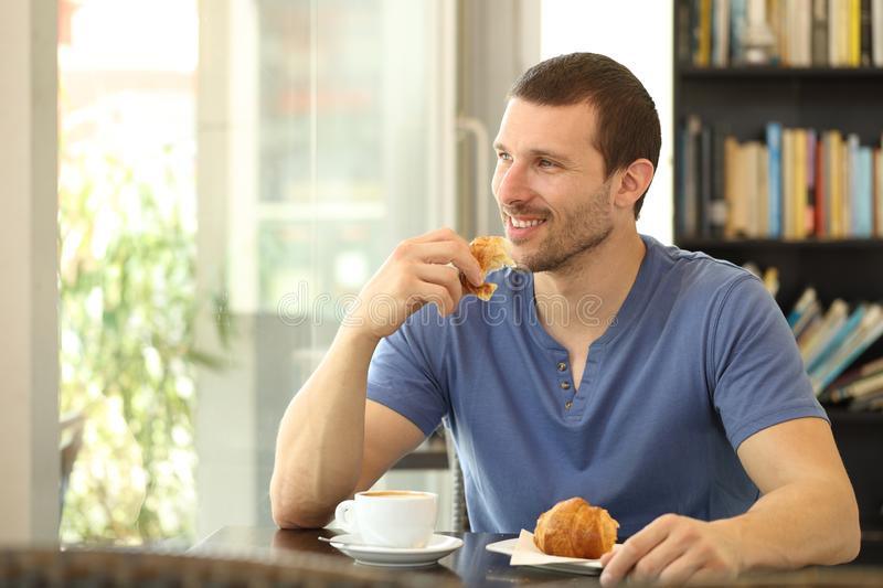 Happy man eating a croissant for breakfast in a coffee shop. Happy man eating a croissant for breakfast sitting in a coffee shop looking through a window stock images