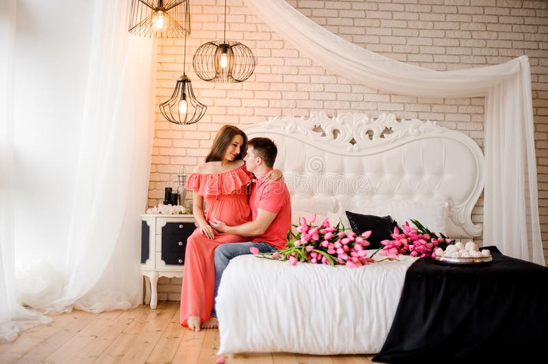 Happy man embracing his young and beautiful pregnant wife stock photography