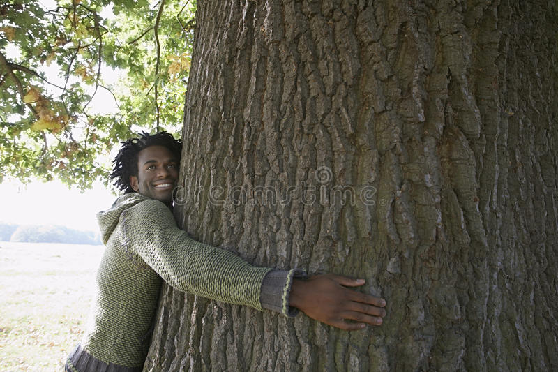 Happy Man Embracing Tree Trunk At Park. Happy young African American man looking away while embracing tree trunk at park royalty free stock photography