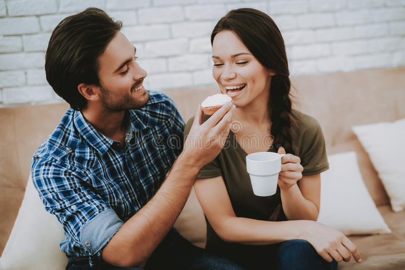 Happy Man Feeding Sandwich Smiling Woman with Cup stock image