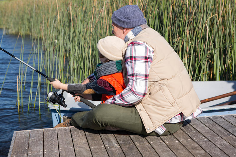Happy man fishing with his son stock photo