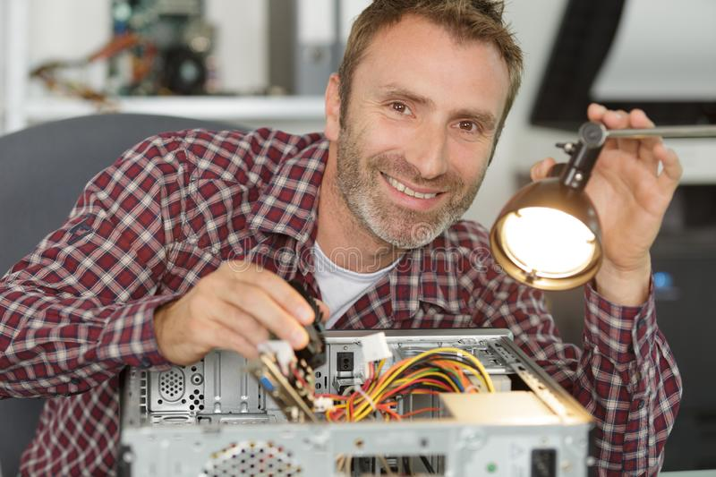 Happy man fixing pc royalty free stock images